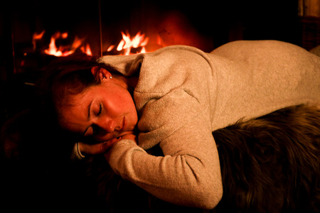 young woman is sitting by the fireplace Stock Photo