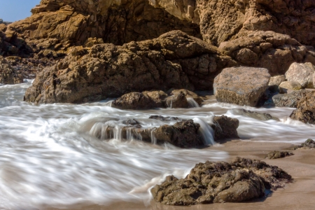 recedes: The Pacific Ocean crashes and recedes at Leo Carrillo State Beach in Malibu, California. Stock Photo