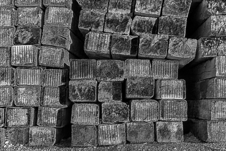 creosote: Stacked Railroad Ties Near the Side of the Tracks in Black and White
