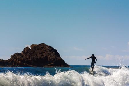 Surfer Comes Ashore at  Leo Carrillo State in Malibu, California.