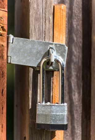 A Closed Wood Gate is Protected by a Strong Lock Close-up.