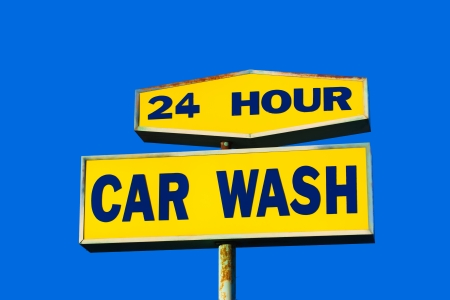 car wash: Worn 24 Hour Car Wash Sign with Blue Sky Background Stock Photo