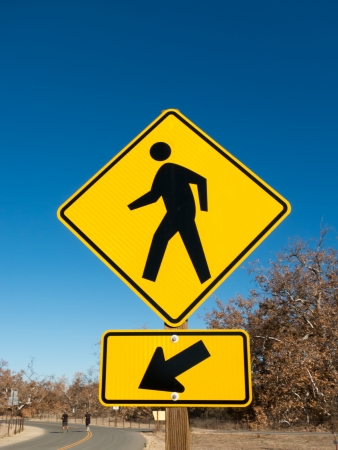 Pedestrian Crossing Vertical Sign With Blue Sky and Road photo