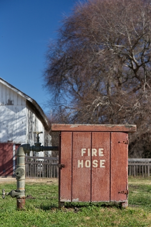 Old Fashioned Fire Hose Box Vertical Image on Rural Farm in the United States photo