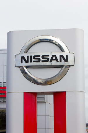 headquartered: MONTEREY, CAUSA - MAY 8, 2014:  Nissan Motors automobile dealership and sign.  Nissan Motors is is a Japanese multinational automotive manufacturer headquartered in Japan.
