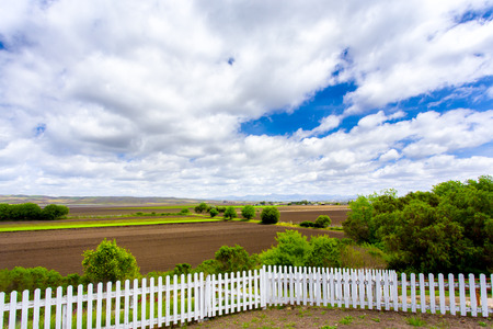 picket green: White Picket Fence  Green Farmland and Dramatic Clouds.