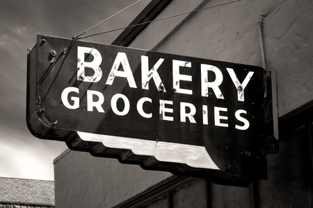 general: Black and White Worn Bakery and Groceries Sign in Small Town