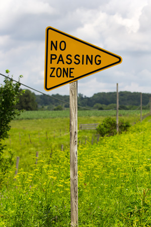 No passing zone sign along rural highway photo