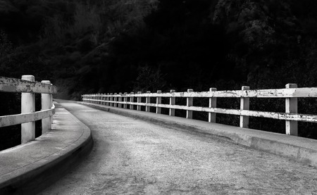 fading: Curved path leading to a road fading to darkness Stock Photo