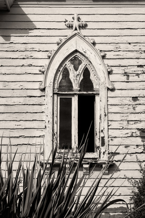 Black and white vertical image of distressed building with curved, antique window photo