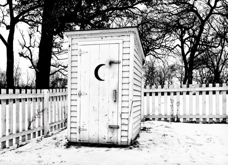 american midwest: Vintage outhouse with picket fence in black and white in the American midwest in Winter. Stock Photo