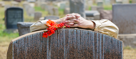 Lone figure of persons hands grieving at cemetery