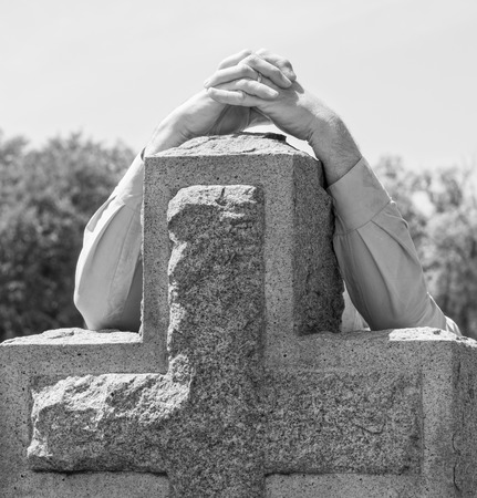 Black and white lone figure of person's hands grieving at cemetery