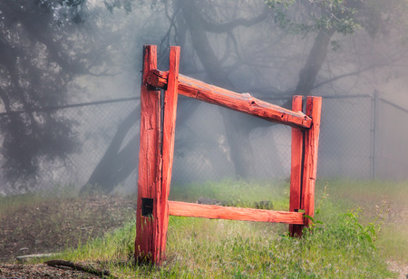 worn structure red: Isolated red stockade fence in forest fog. Stock Photo