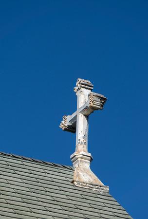 christian halloween: Ornate worn and peeling church cross against blue sky.