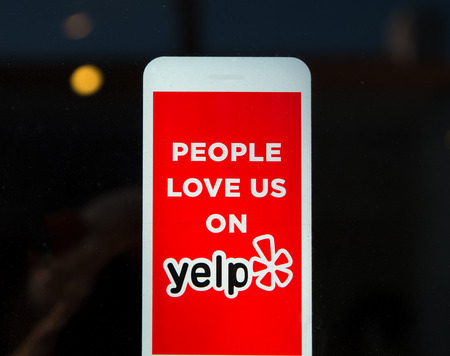publishes: LOS ANGELES, CAUSA - November 11, 2015: Yelp emblem on restaurant exterior. Yelp publishes on-line reviews about businesses.
