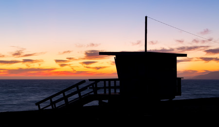 zuma: Lifeguard stand at dusk in silhouette at Zuma Beach in Malibu, California.