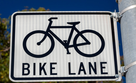bike lane: Bike lane parking sign with icon of bicycle and prominent black lettering.