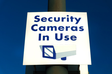 security monitor: Security cameras in use sign in municipal public area. Stock Photo