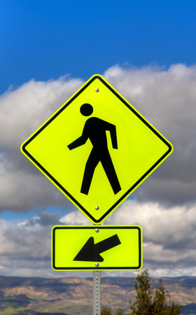 crosswalk: Yellow crosswalk sign with human icon and arrow pointing left.