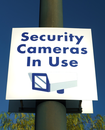 security cameras: Security cameras in use sign in municipal public area. Stock Photo