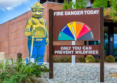 smokey: ACTON, CAUSA - MAY 7, 2016: Smokey Bear mascot and fire danger sign. Smokey the Bear is an advertising mascot to educate the public about forest fires.