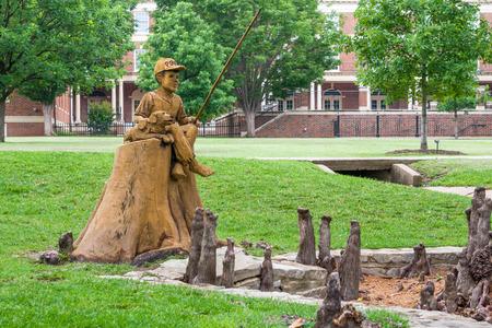 STILLWATER, OK / USA - 2016 년 5 월 20 일 : 오클라호마 주립 대학 캠퍼스의 Theta Pond에서 소년과 개 낚시 조각.