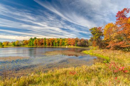 Sunlit autumn lake in the American Midwest near Balsam Lake, Wisconsin. 免版税图像