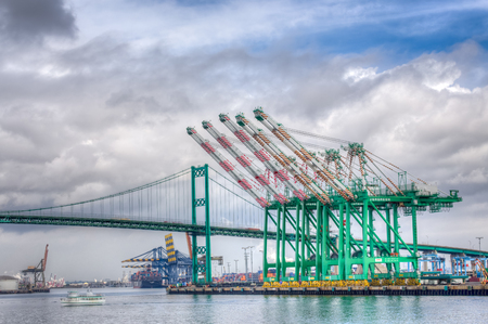 SAN PEDRO, CAUSA - JANUARY 18, 2016: Evergreen Marine Corporation Container Cranes with the Vincent Thomas Bridge in background at Port of Los Angeles.
