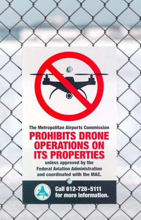 faa: MINNEAPOLIS, MNUSA - JANUARY 14, 2017: Sign attached to chain link fence prohibiting drones at airport in the United States.