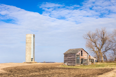 Abandoned and dilapidated farm house and silo in the American midwest in Autumn.