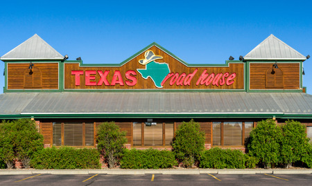 specializes: SIOUX FALLS, SDUSA - JUNE 4, 2017: Texas Roadhouse exterior sign and logo. Texas Roadhouse is an American chain restaurant that specializes in steaks and promotes a Western theme. Stock Photo