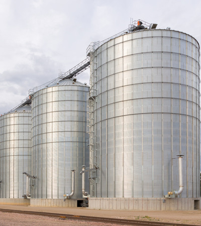 Round metal grain elevator bins in vertical next to railroad tracks in the United States.