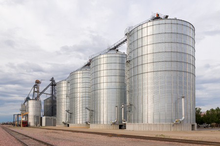 warehouse: Round metal grain elevator bins next to railroad tracks in the United States.