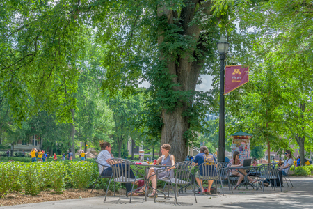 MINNEAPOLIS, MN/USA - JUNE 28, 2018: Unidentified individuals seated at the Northrop Mall on the east bank of the University of Minnesota. Editorial