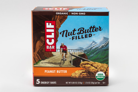 ST. PAUL, MN/USA - FEBRUARY 24, 2019: Clif Bar peanut butter energy bar container and trademark logo. Clif Bar & Company is an American company that produces organic foods and drinks.