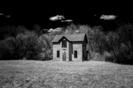 Darkened brick abandoned farm house in secluded forest in black and white.