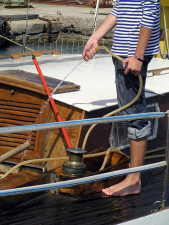 The sailor washes a deck on a sports sailing yacht from a tree Stock Photo