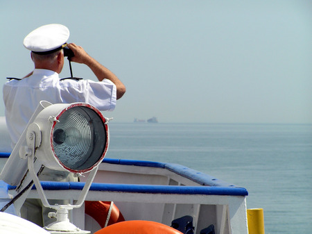 The captain of a vessel in the white form looks at horizon through the field-glass