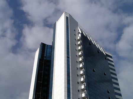 White and dark blue office high-altitude building on a background of the sky