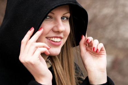 The face and hands of the young girl correcting a black hood Stock Photo