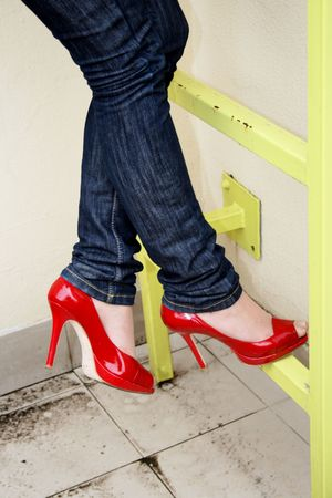 high heeled: Harmonous legs in jeans and red shoes on a yellow metal ladder Stock Photo