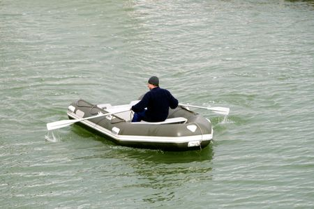 The man rows with oars and floats on a rubber inflatable boat on the sea