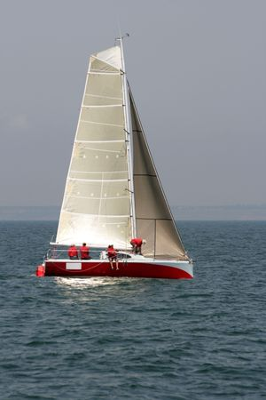 The command of seamen prepares for start of a regatta on a red yacht with gold sails