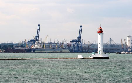 White stone beacon in water area of port on a background of moorings with loading technics and a grain complex
