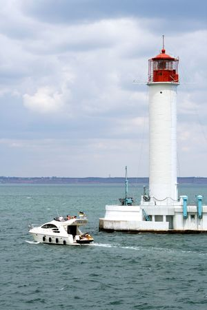 The motor yacht floats by the big beacon Stock Photo