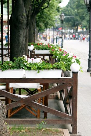 street cafe fenced by a wooden fence decorated by flowers