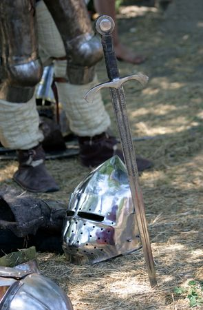 Sword will thrust beside with a helmet laying on the ground