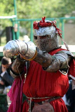 The knight in red puts on a metal glove Stock Photo