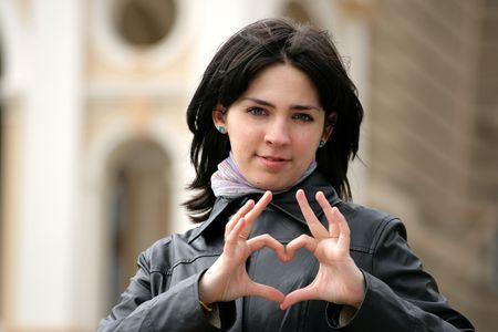 young girl in the street shows heart symbol photo